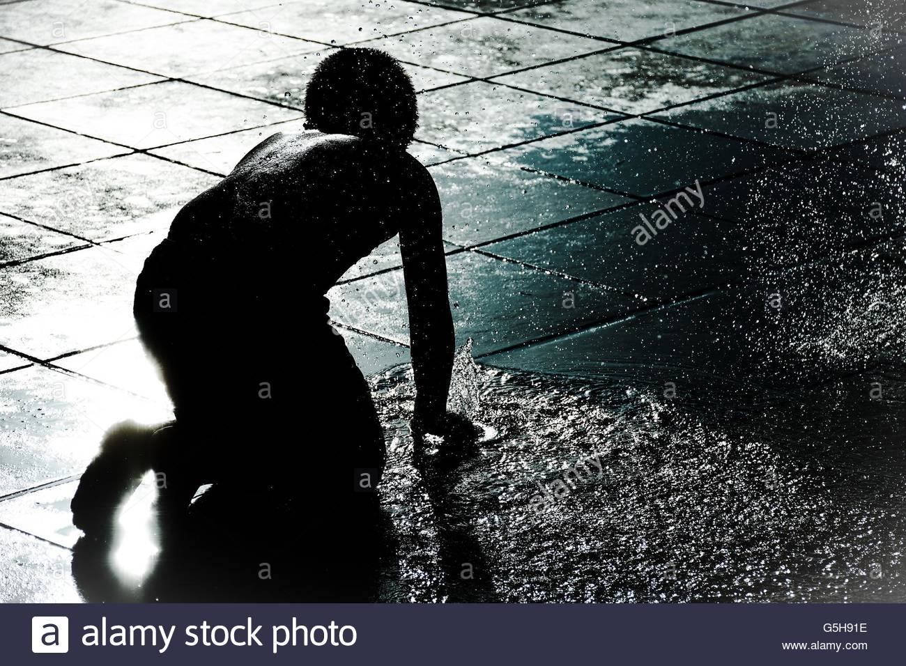 Boy playing with water - Stock Image
