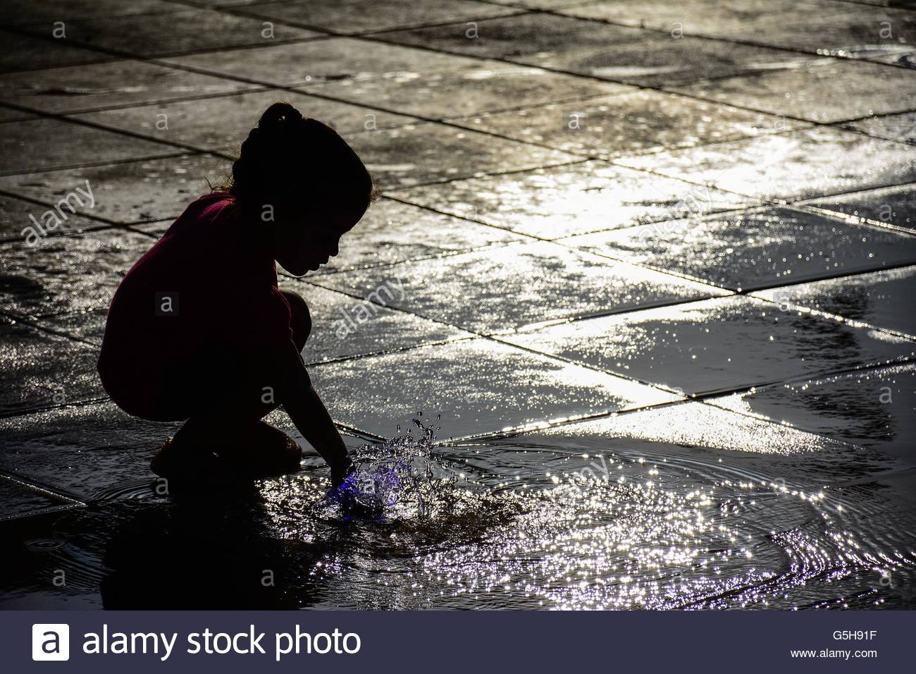 Little girl playing with water - Stock Image