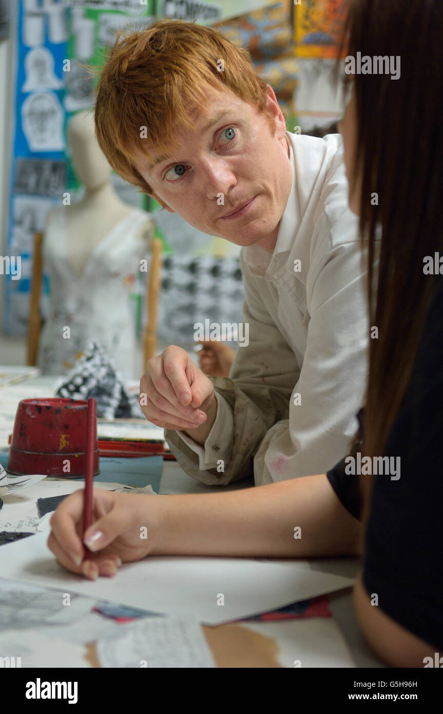 Secondary school art teacher teaching in the classroom. England. UK - Stock Image