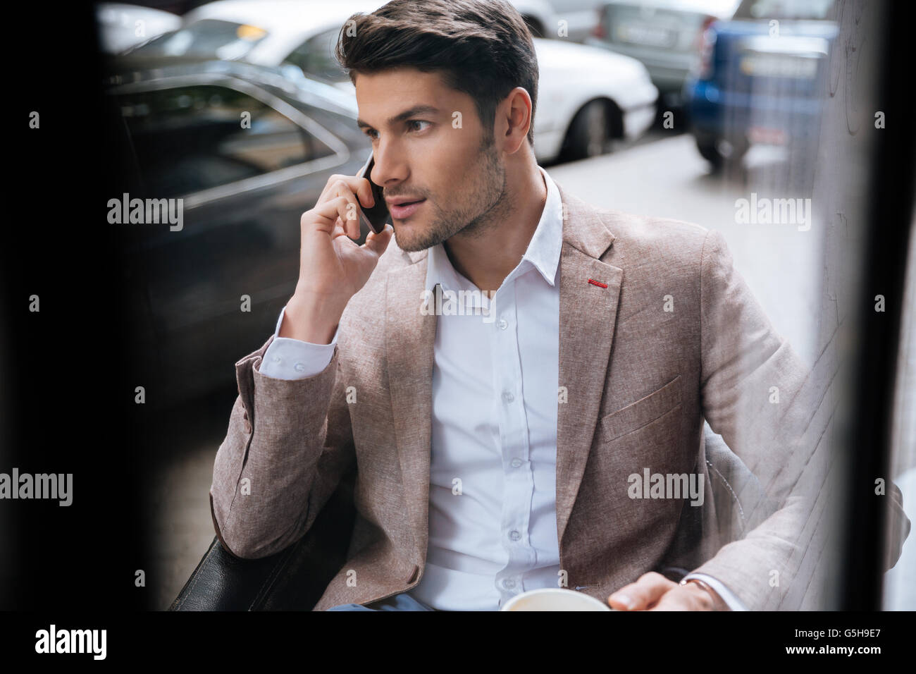 Attractive young businessman sitting and talking on mobile phone sitting outdoors in cafe - Stock Image