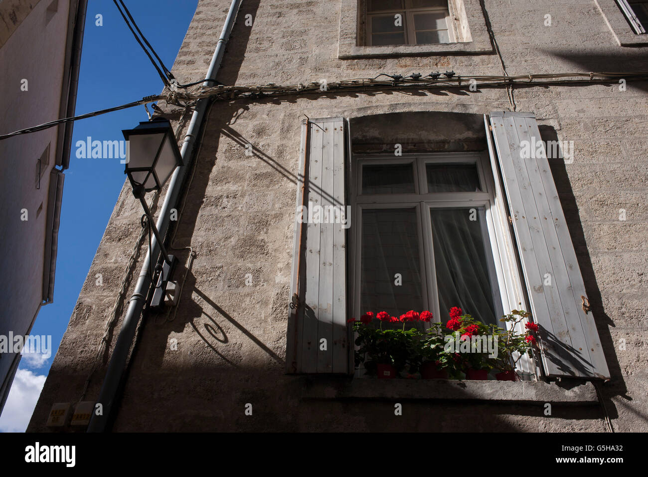 Red carnations in a window box of an apartment on a narrow street corner in old Montpellier, south of France. - Stock Image