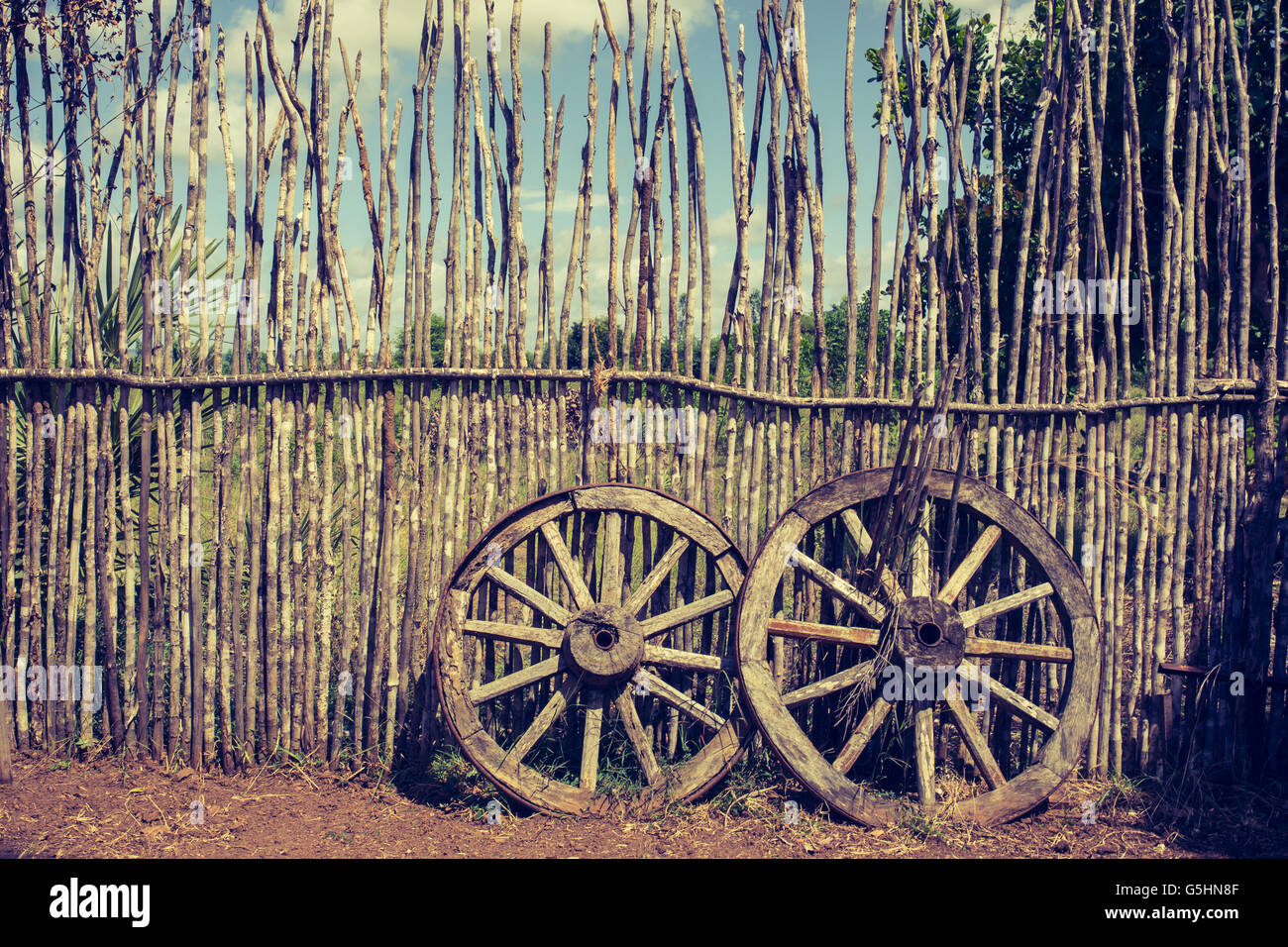 Two old wagon wheels near the wooden fence. Old cart wheel as symbol and concept of fortune and fate. Old fashioned - Stock Image