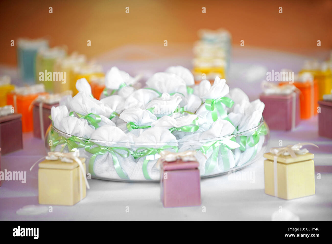 Assorted party favors displayed on a table with colorful gift boxes tied with bows and a bowl of little bags tied - Stock Image