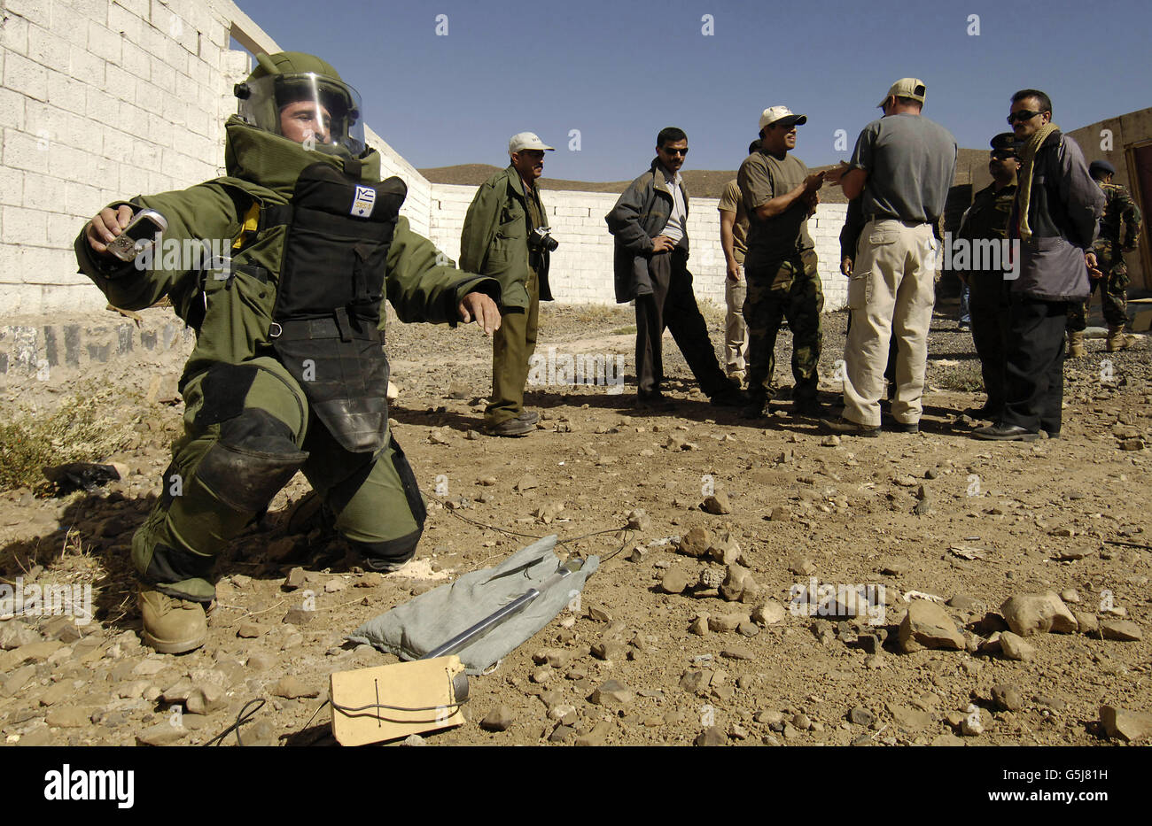Yemen explosive ordnance disposal team members watch a Petty Officer, dressed in a bomb suit, destroy an explosive - Stock Image