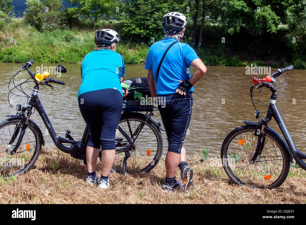 Two cyclists with their electric bikes watching river - Stock Image
