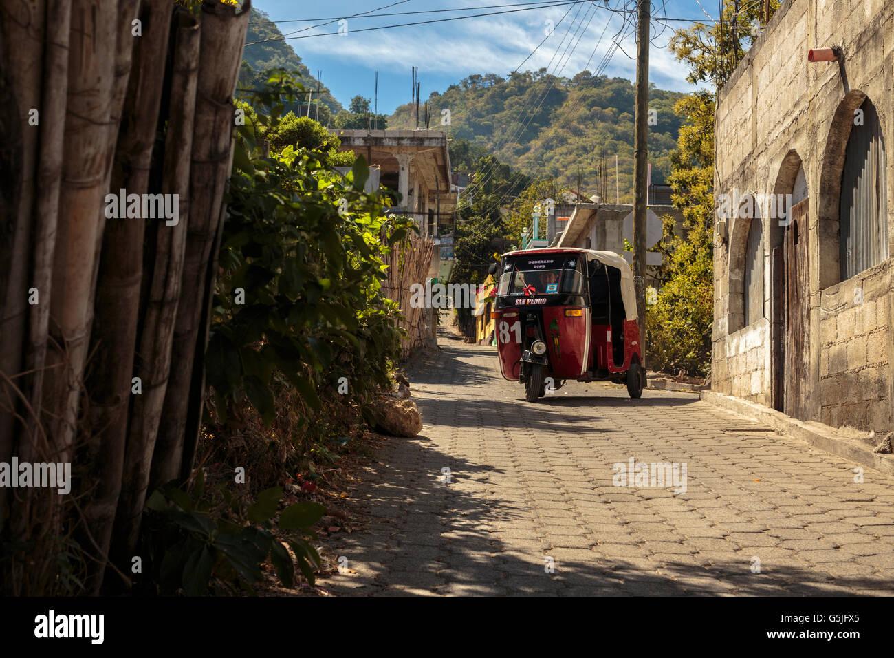 A motocar taxi navigates the streets of San Pedro La Laguna in Lake Atitlan Guatemala, a popular tourist destination. - Stock Image