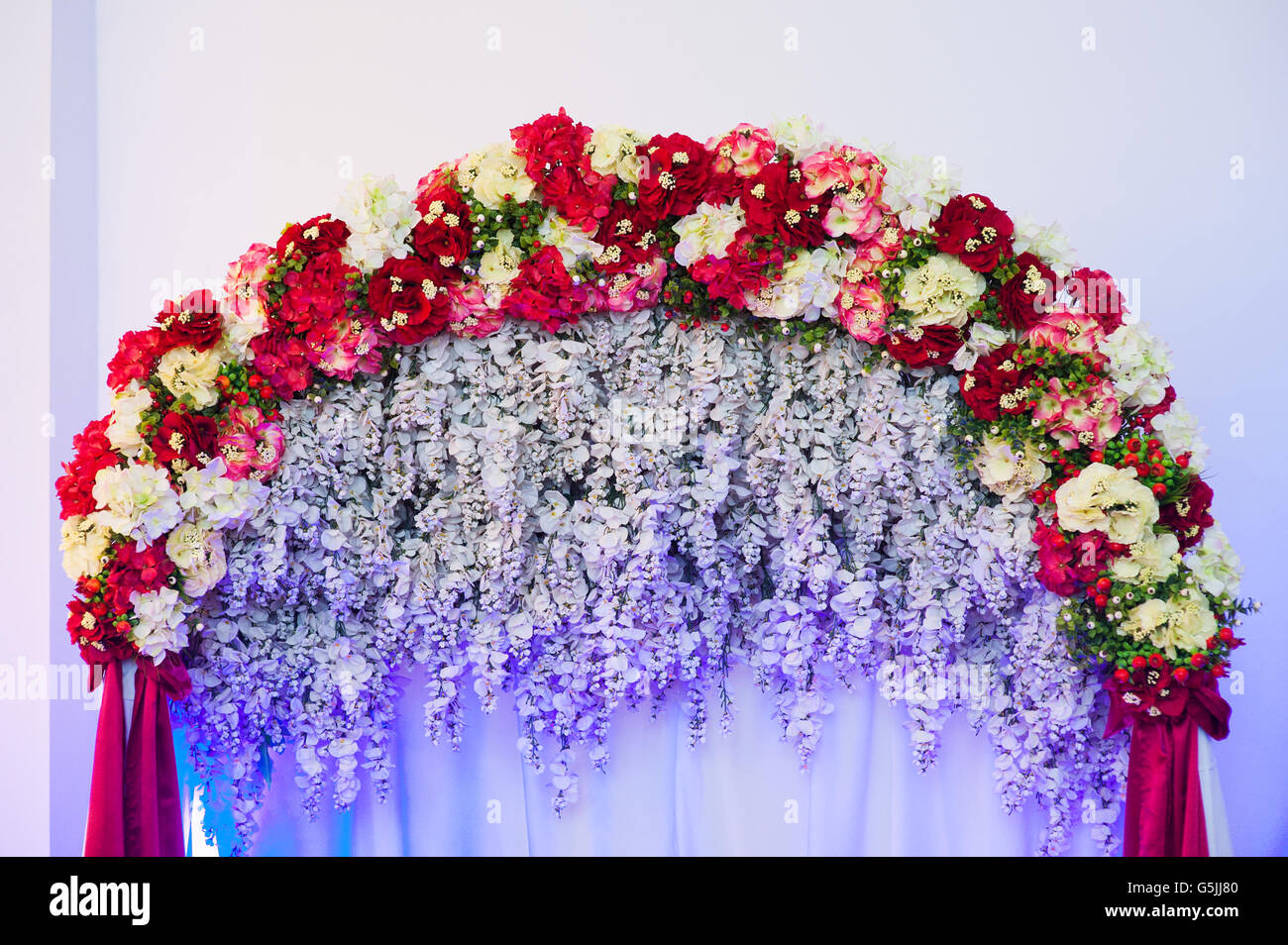 Beautiful wedding arch decorated with pink and red flowers indoors beautiful wedding arch decorated with pink and red flowers indoors junglespirit Choice Image