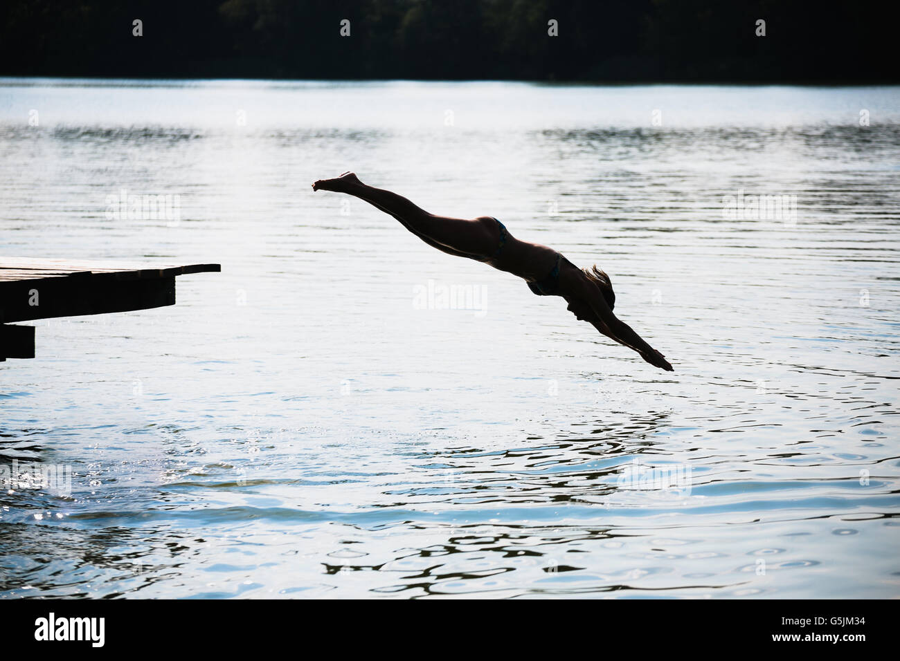 woman jumping into the lake Stock Photo