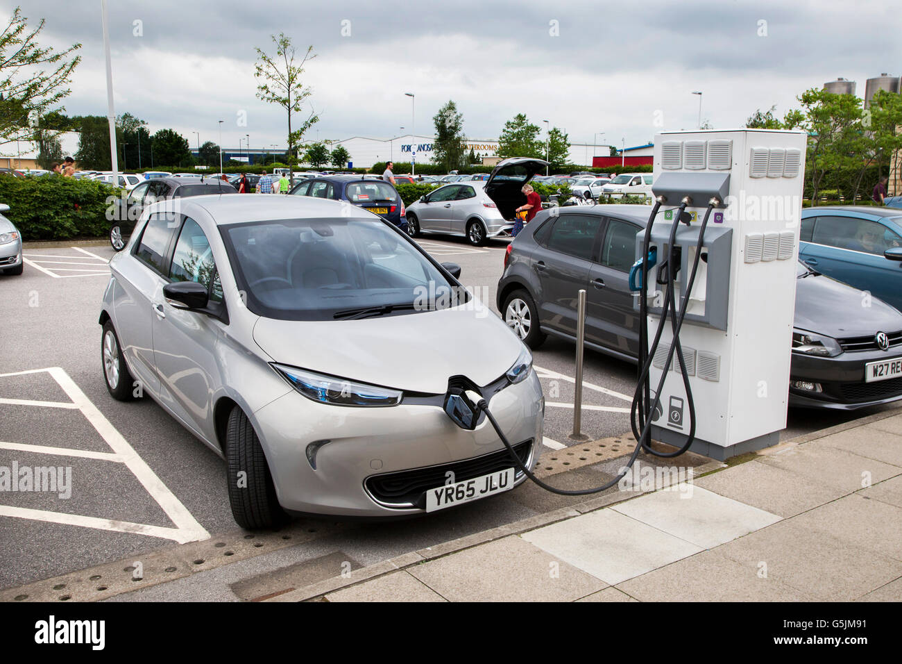 Electric Renault car charging at a recharging point in the car park of a retail shoppping outlet in Doncaster South - Stock Image