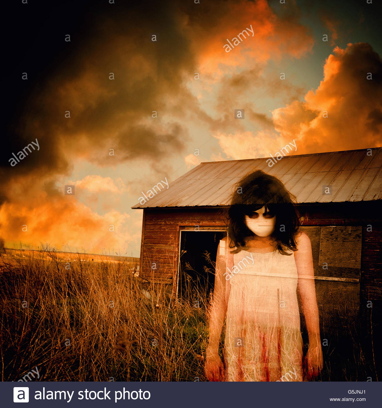 A scary ghost girl is wearing a white dress and an abandoned house shed is in the background with storm clouds for - Stock Image
