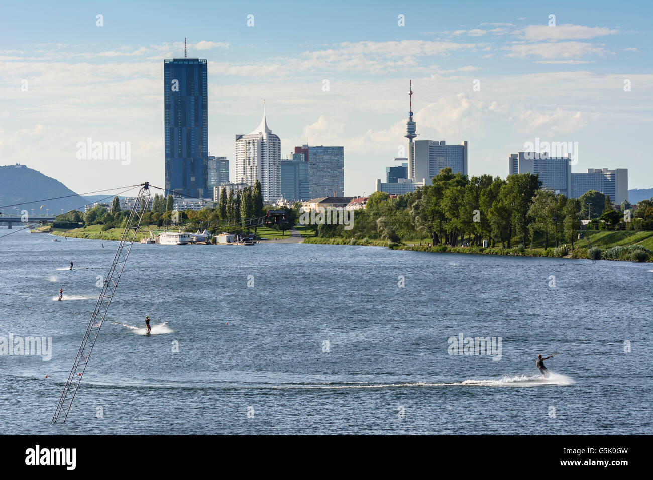 Wakeboarding with a water ski lift in the New Danube before the DC Tower 1 , the skyscraper New Danube and the Vienna - Stock Image