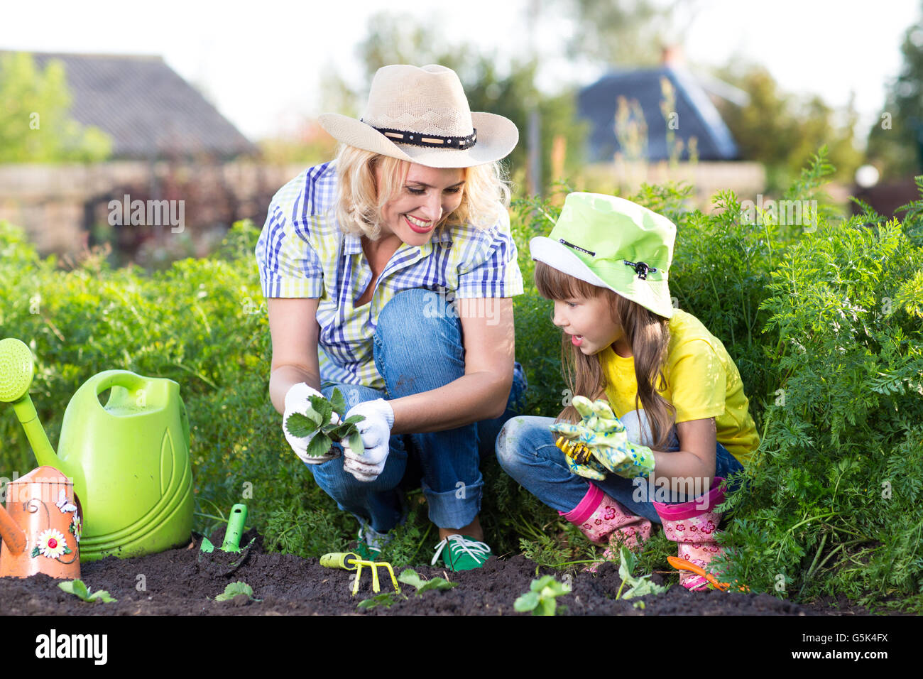 Mother and daughter child planting strawberry seedlings in summer Stock Photo