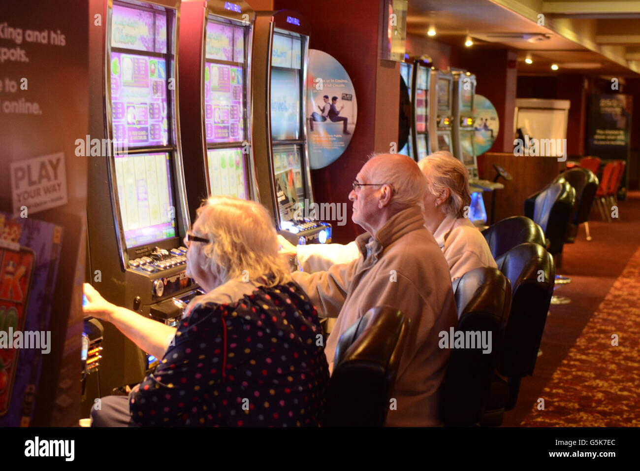 People play gambling machines in a high street casino. - Stock Image