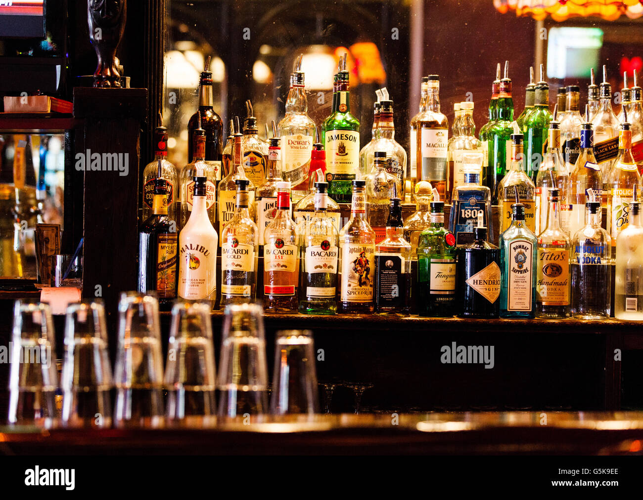 A collection of assorted, alcoholic, branded spirit or liquor bottles, displayed on a shelf at the back of a public - Stock Image