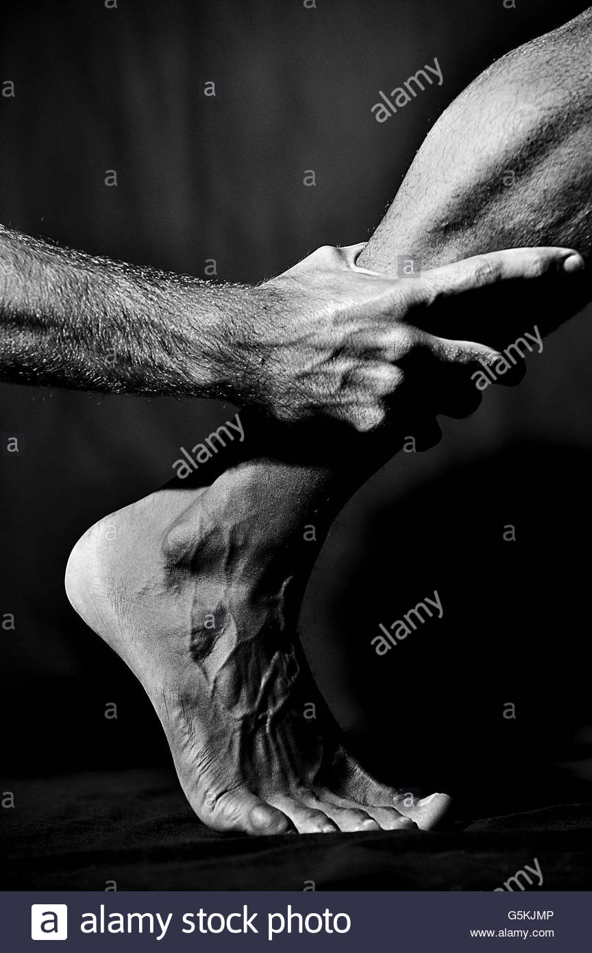 Masculine hand holding a males calf - Stock Image