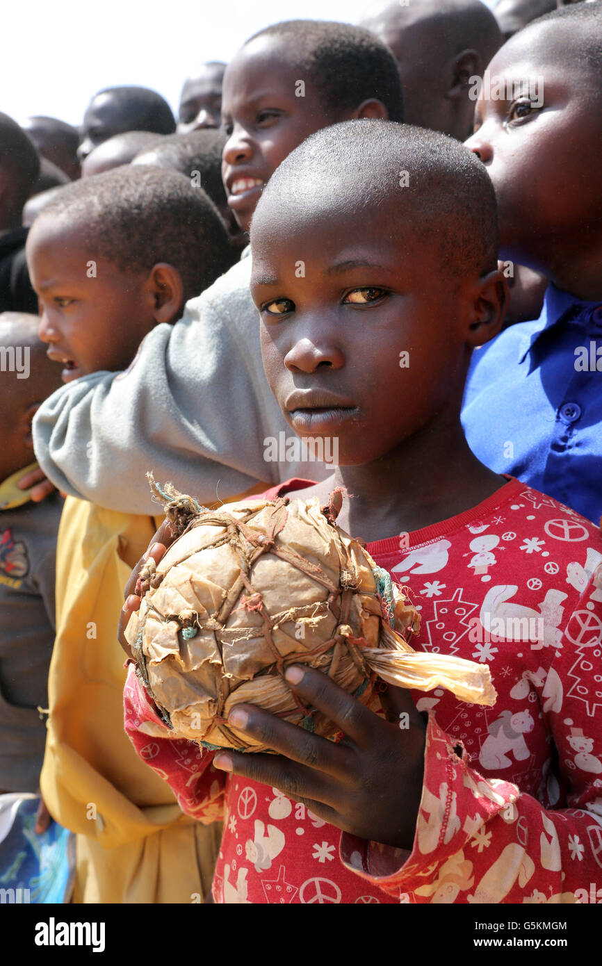 Young boy (10 years) with his self-made football made of fabric scraps and plastic bags in a village in Gikongoro - Stock Image