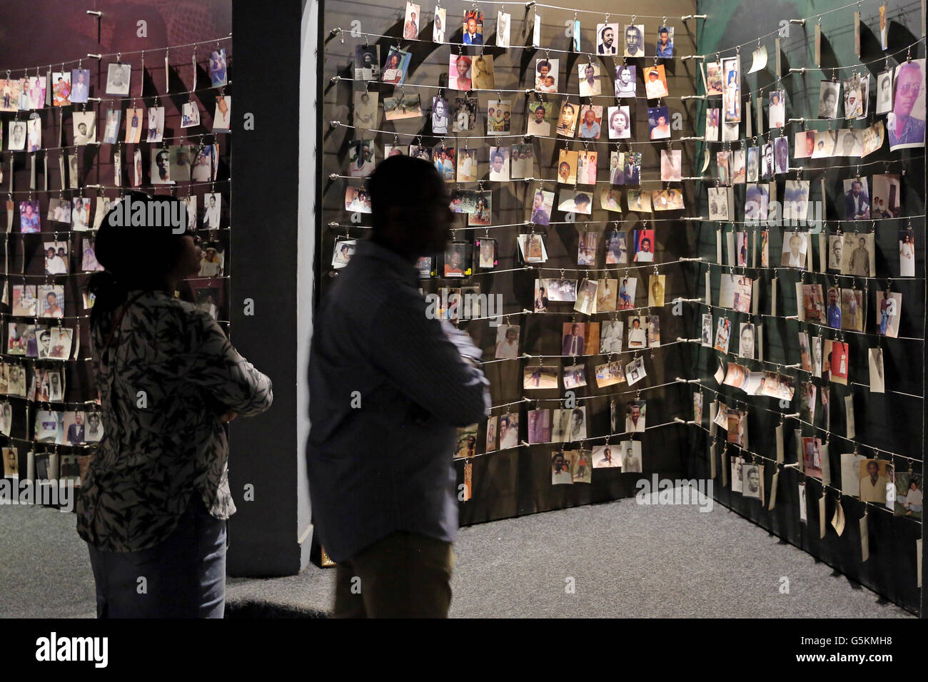 Visitors looking at photographs (donated to the museum by families) of people who were killed during the 1994 genocide. - Stock Image