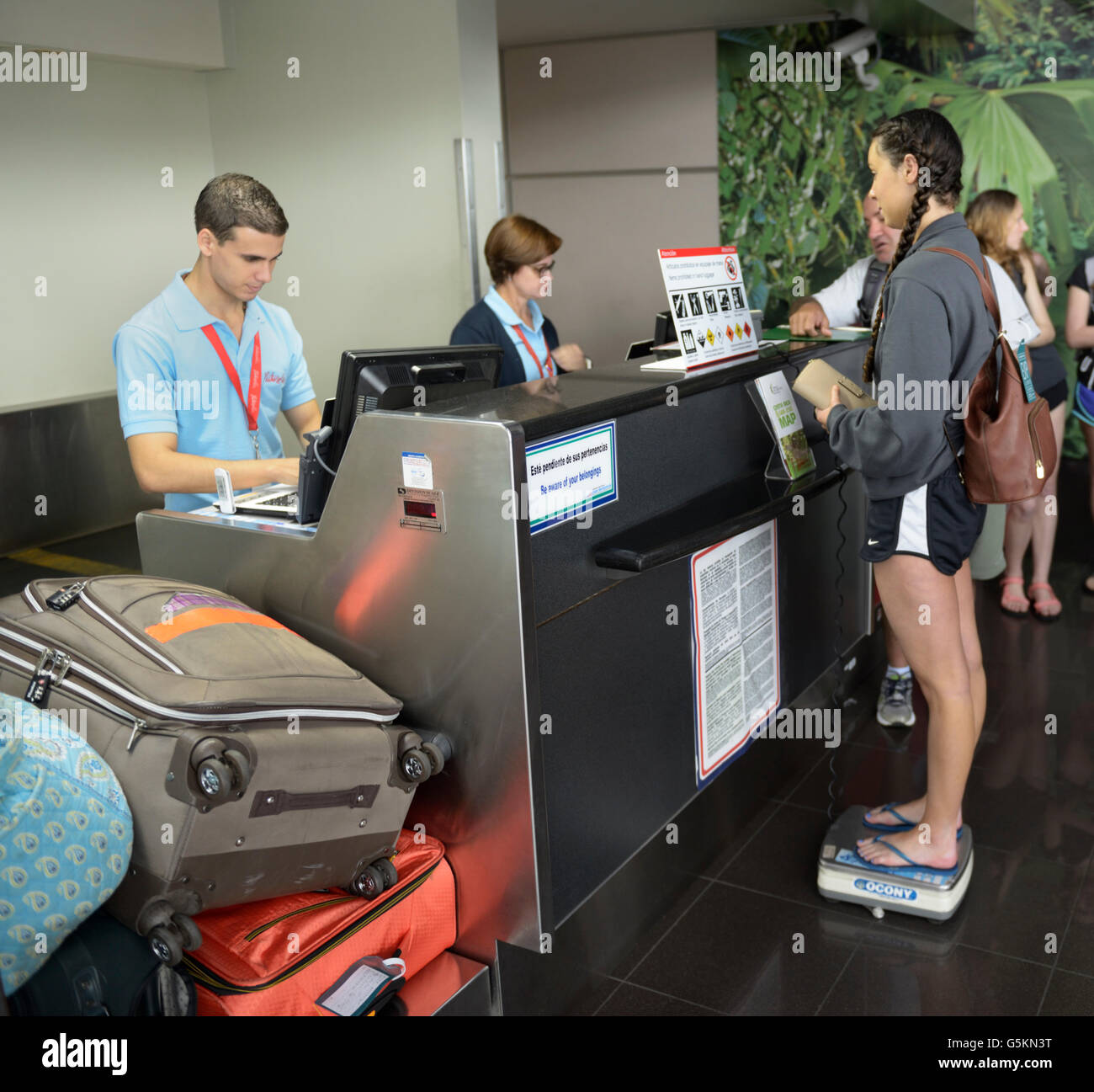 Weigh-in of traveler and luggage at airport before boarding small plane, San Jose, Costa Rica - Stock Image