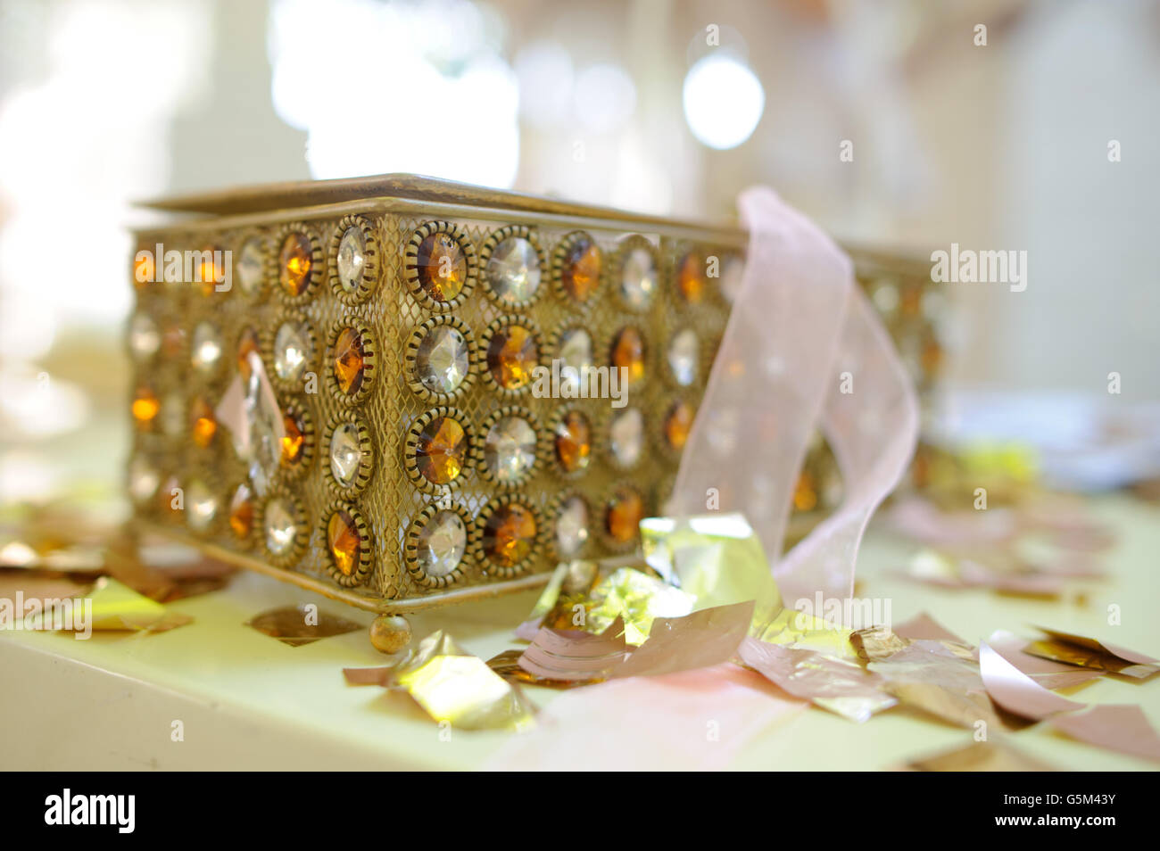 She is on the surface covered with confetti of gold color. The casket is decorated with a large amount of white - Stock Image