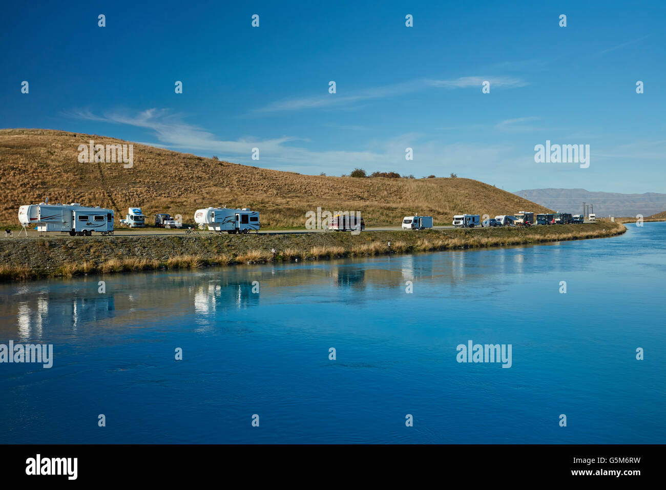 People fishing, caravans and campervans by Lake Ruataniwha, near Twizel, Mackenzie District, South Canterbury, New - Stock Image