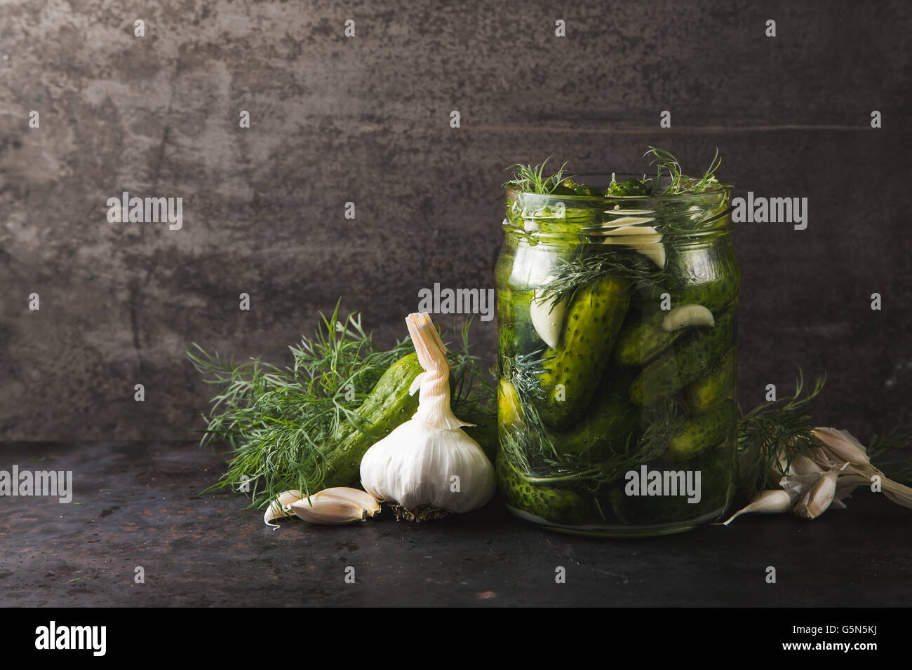 Glass jar of pickles with dill and garlic - Stock Image