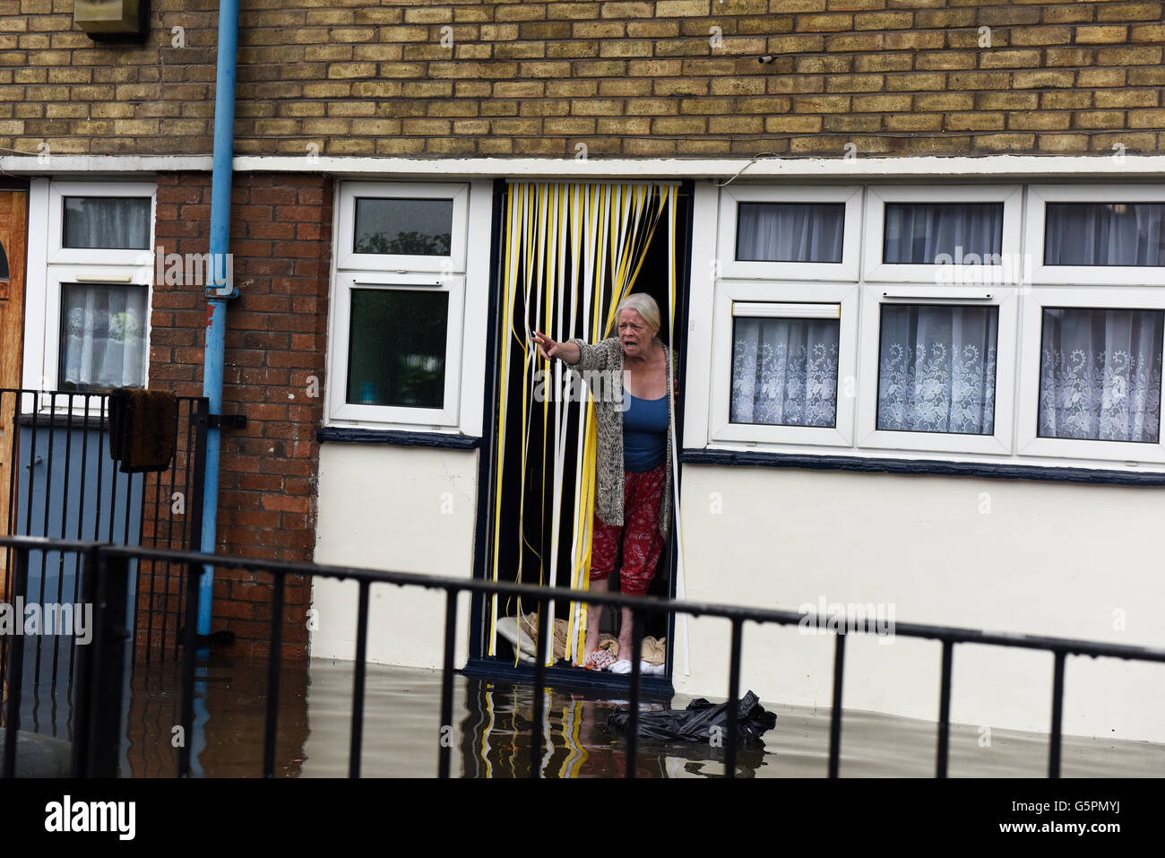 London, UK. 23rd June 2016. Heavy rain causes flooding in East London, Canning Town. Stressed woman seen standing - Stock Image