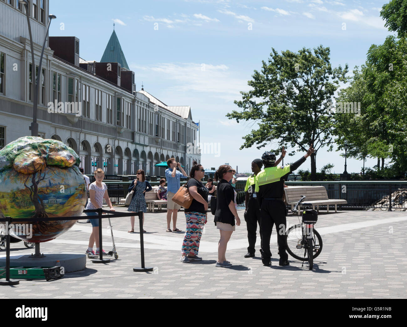 Two Battery Park City (BPC) Ambassadors helping tourists with directions near Pier A, Battery Park, New York. - Stock Image