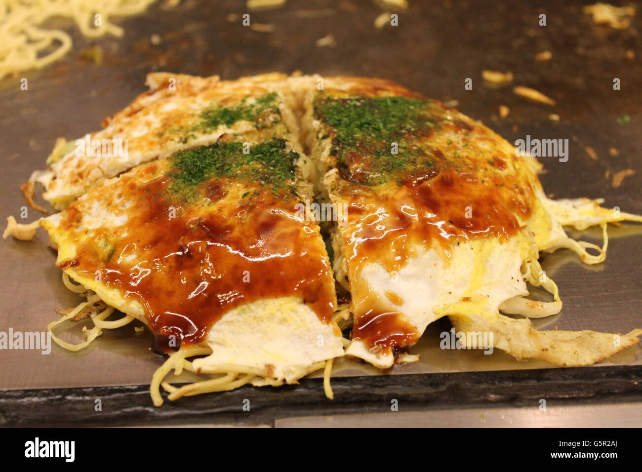 Mouth-watering Okonomiyaki, served Hiroshima-style in Hiroshima, Japan - Stock Image