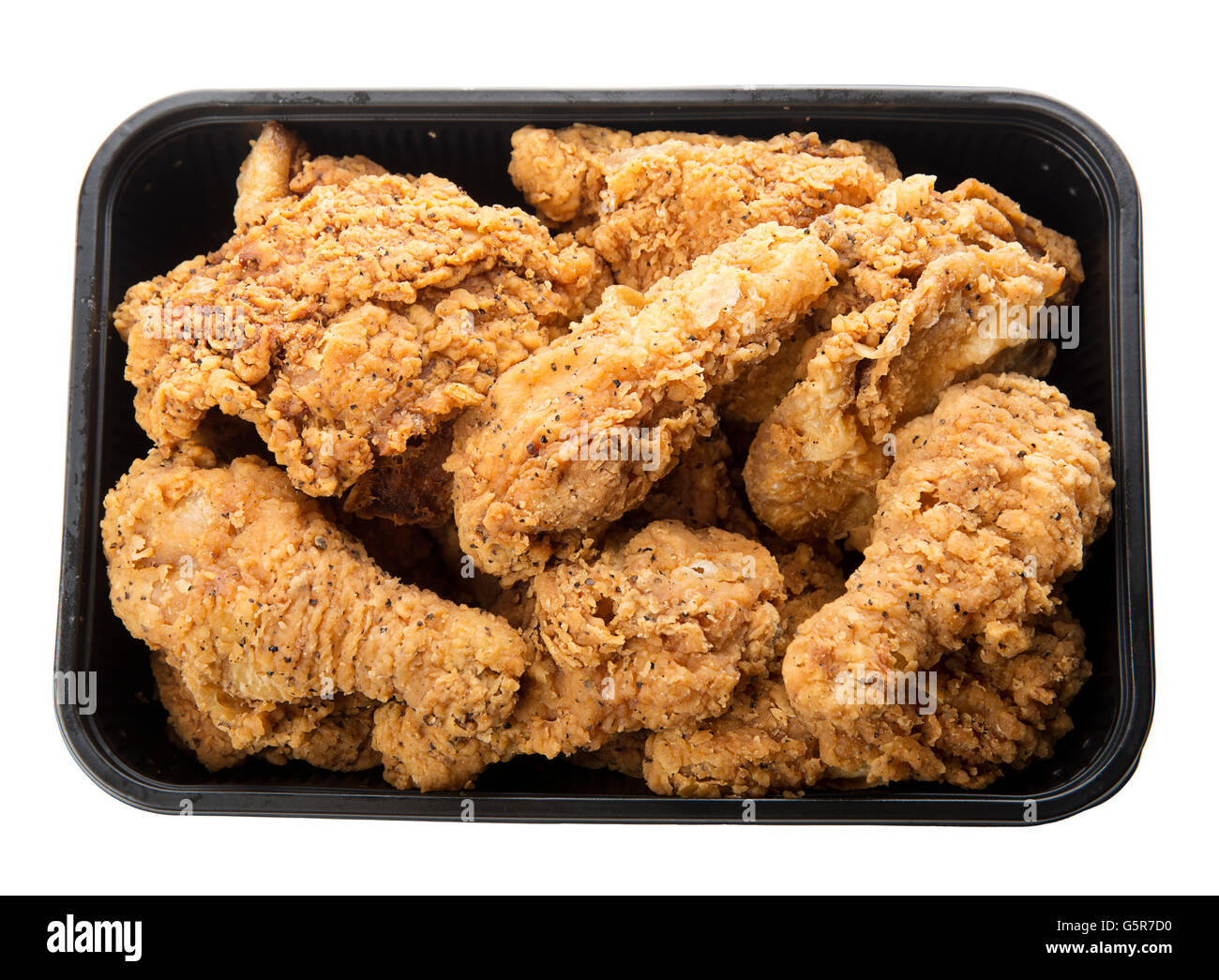 Close up of fried chicken in a plastic container isolated on white - Stock Image