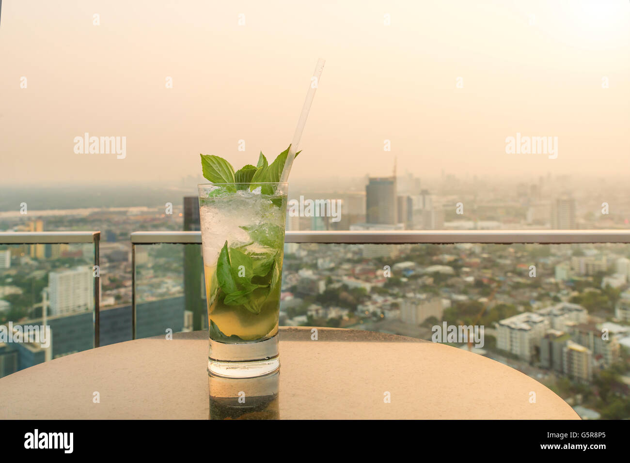 Mojito cocktail on table in rooftop bar. Rooftop bar in Bangkok, Thailand. Rooftop bar with sunset. - Stock Image