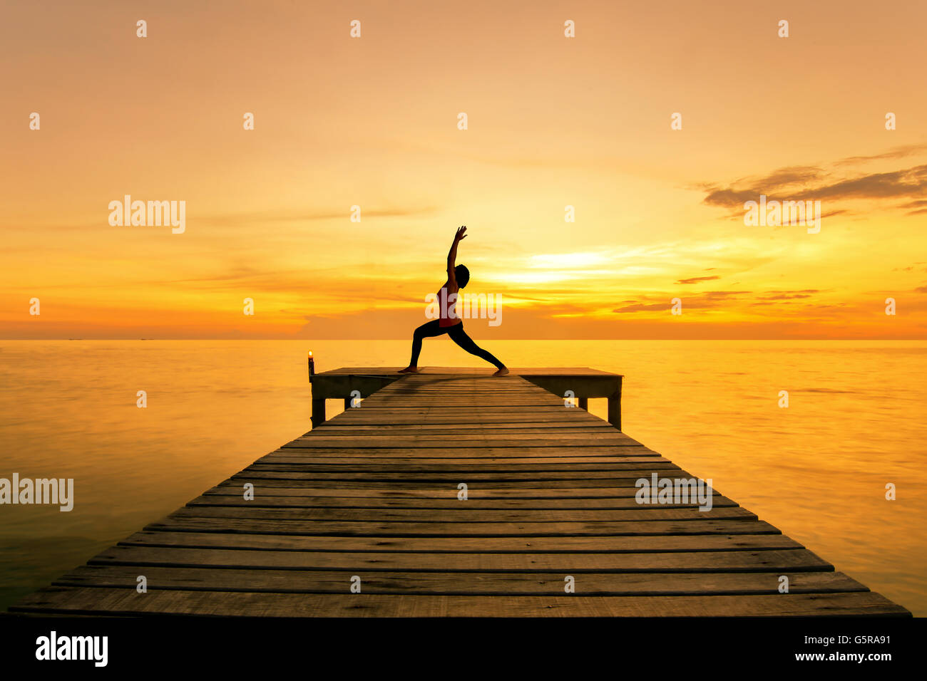 Yoga pose - Woman silhouette practicing yoga Warrior pose on sea bridge at sunset.Yoga near beach. - Stock Image