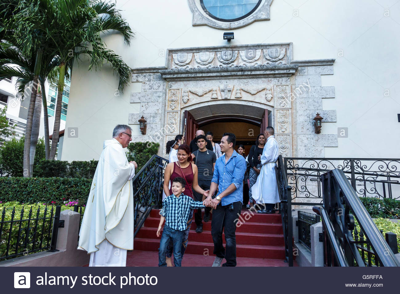 Miami Florida Beach St. Francis De Sales Catholic Church members after service leaving Hispanic man priest greeting - Stock Image