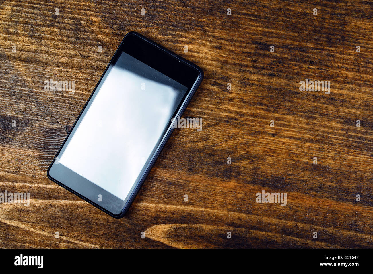 Used smart phone on wooden office desk, blank screen as copy space, flat lay top view - Stock Image