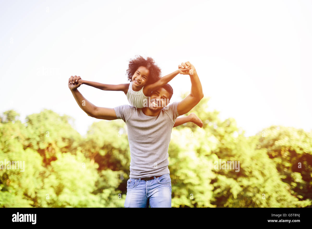 Child flying on father shoulders while held piggyback - Stock Image