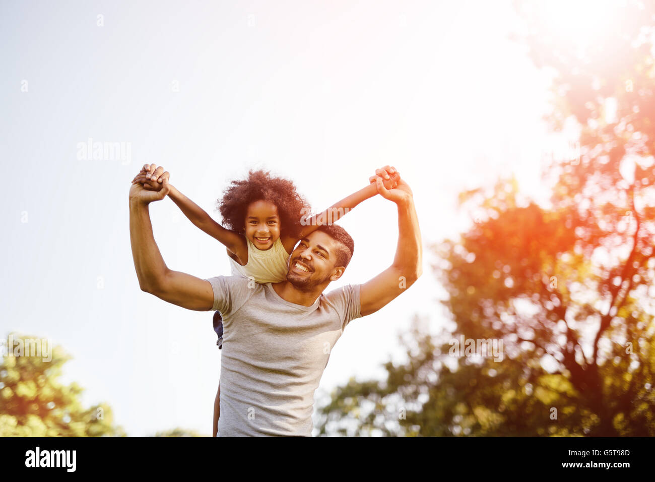 Father carrying daughter piggyback and being truly happy - Stock Image