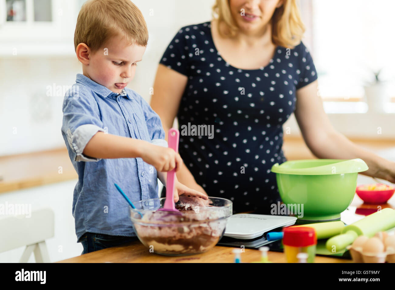 Beautiful child and mother baking in kitchen with love - Stock Image