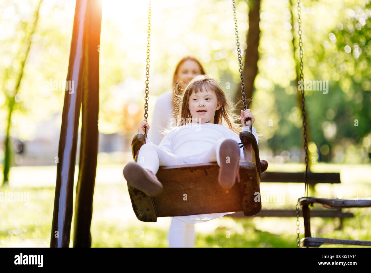 Disabled child enjoying the swing outdoors with sister - Stock Image