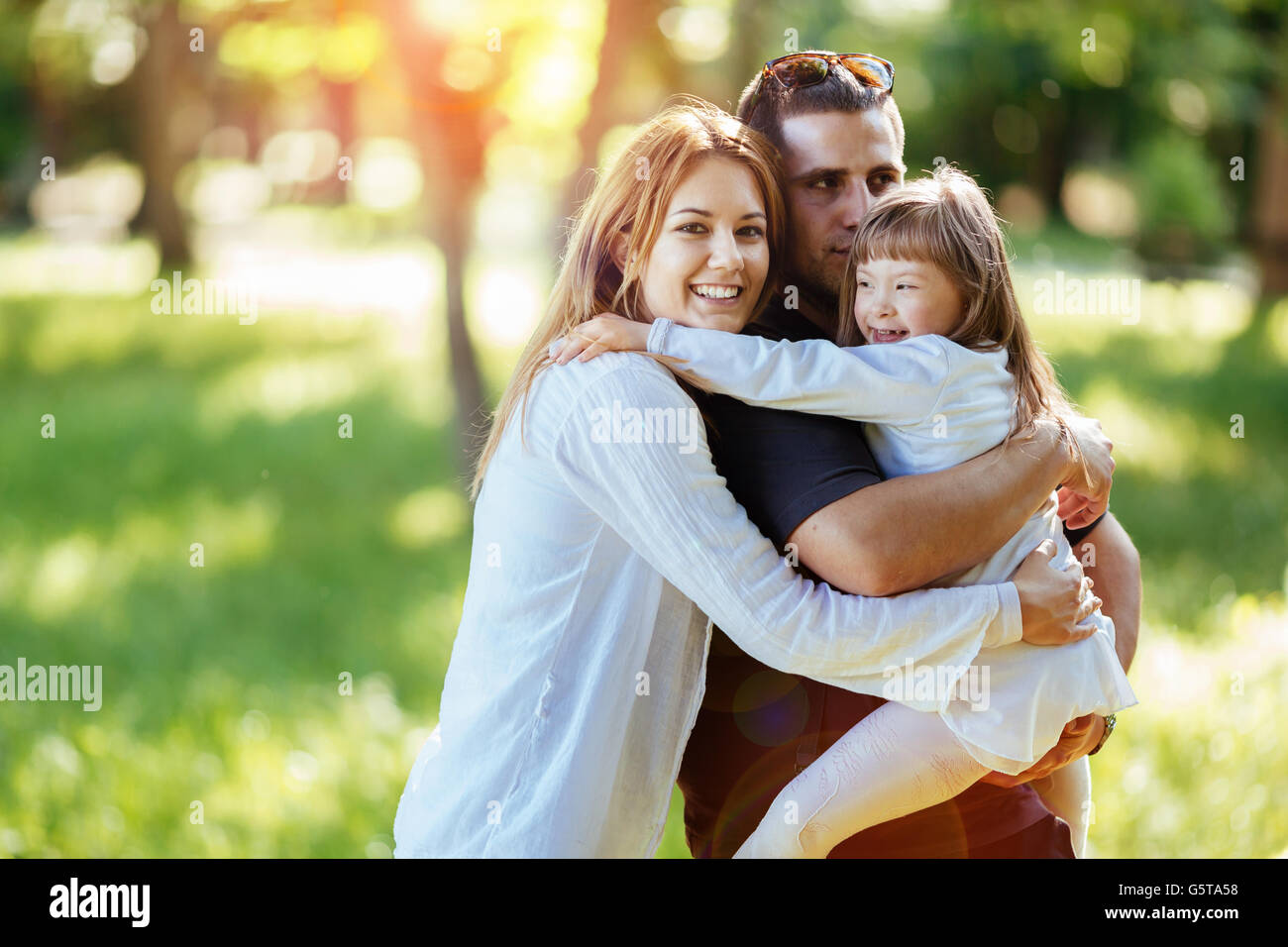 Family happy outdoors with adopted child born with down syndrome - Stock Image