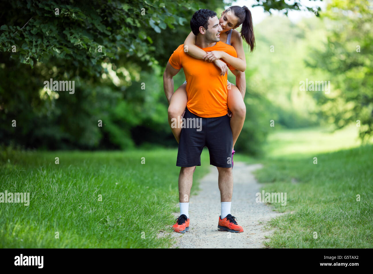 Man carrying woman piggyback after jogging is done - Stock Image