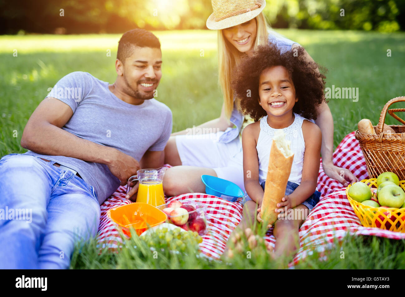 Family picnicking outdoors with their cute daughter - Stock Image