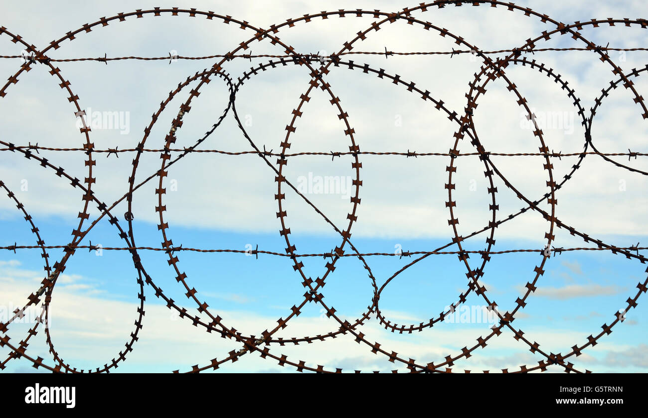 Patterns and shapes in a tangled barbed wire fence with sky Stock ...