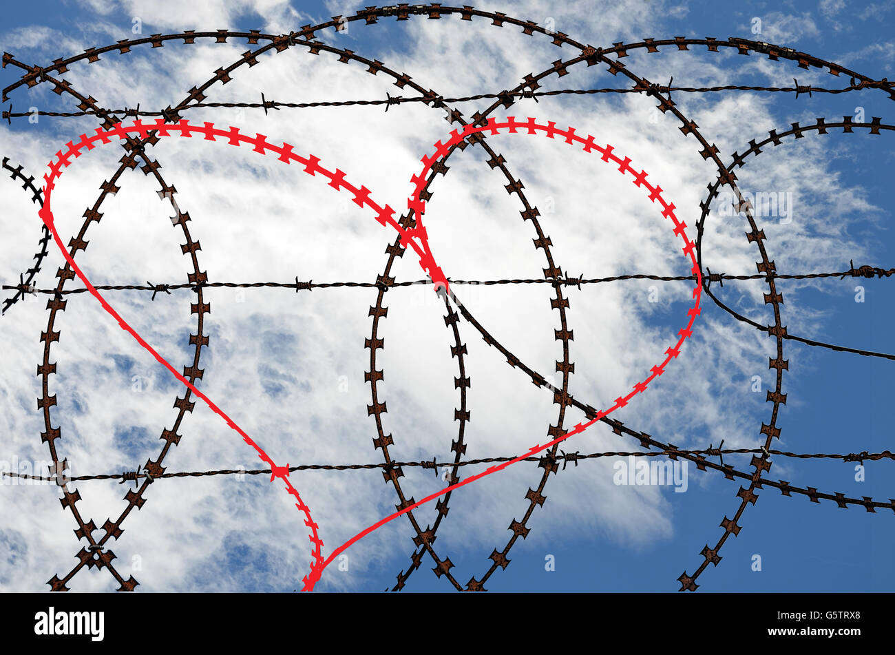 Natural heart shape (digitally coloured red) in a barb wire fence on sky background. Love, freedom, peace and compassion - Stock Image