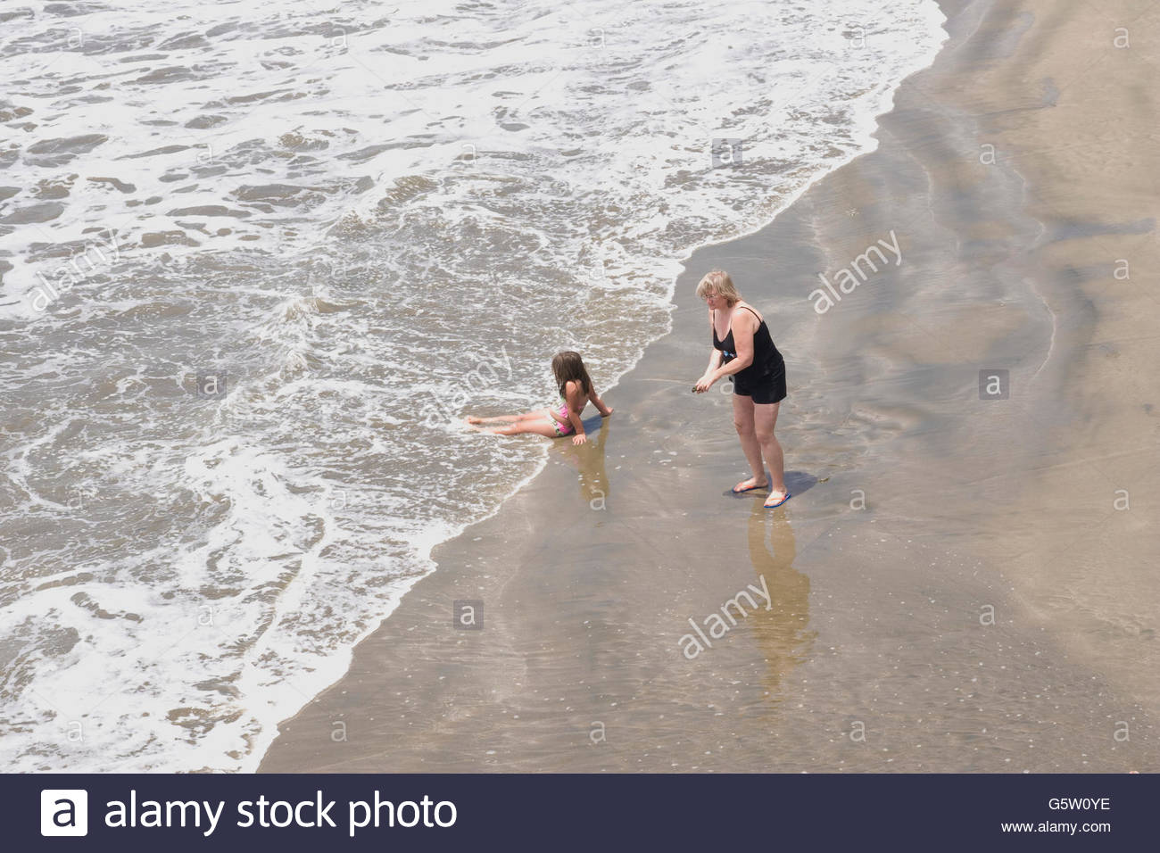 Elevated view of a beach with a woman standing with a girl - Stock Image