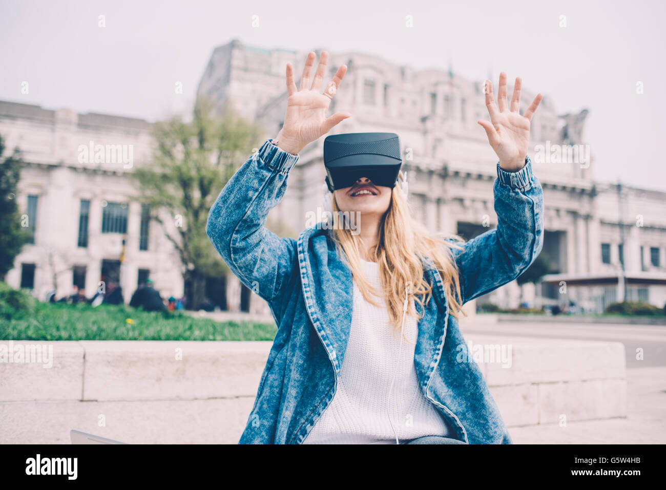 Young beautiful blonde caucasian business woman sitting using 3D viewer - futuristic, multitasking, technology concept - Stock Image