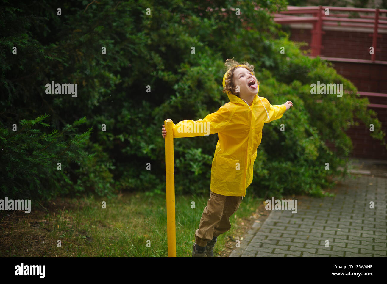 Boy in a yellow raincoat stand under a drizzle. He holds a support in the yard of the house and imagines something - Stock Image