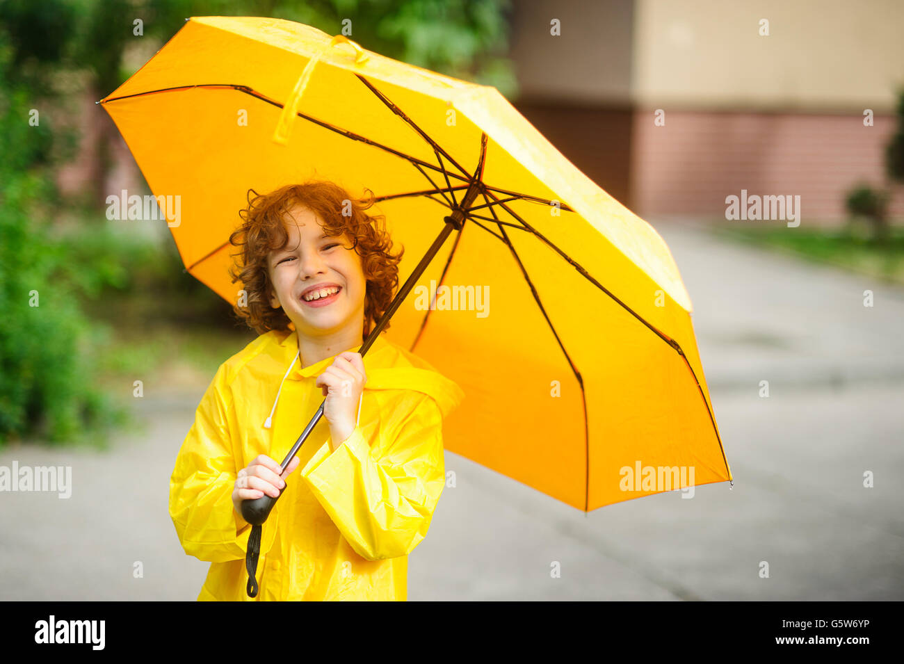 The cheerful boy under a yellow umbrella. The child with a smile looks in the camera having squinted. It has wild - Stock Image