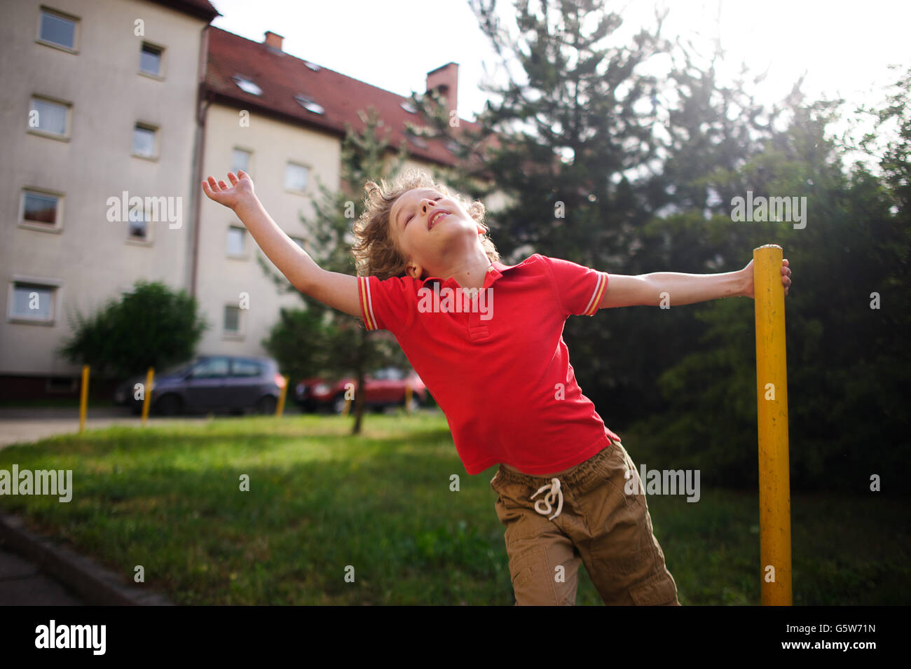 The little boy of 8-9 years turns around a support in the yard of the house. He imagines something during game. - Stock Image