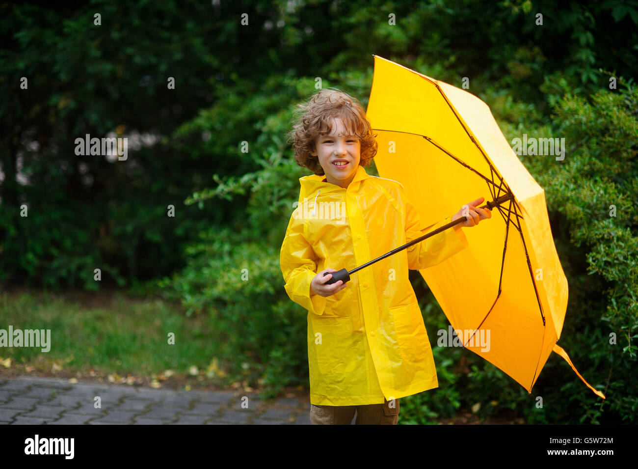 The boy in a raincoat with an umbrella in hands. The cute little fellow dressed in a yellow raincoat holds a yellow - Stock Image