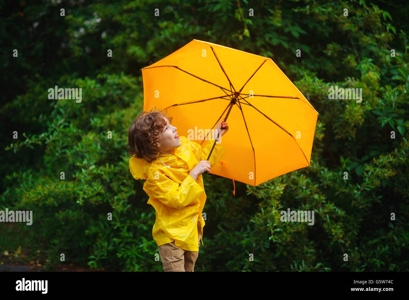Boy of 8-9 years with a yellow umbrella. Cute chappie dressed in a yellow raincoat. The rain has ended and the boy - Stock Image