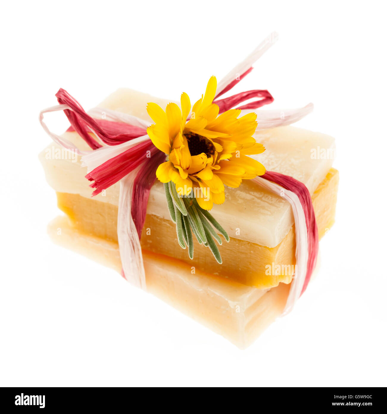 Several herbal handmade artisan soap pieces tied with fresh flowers isolated on white background - Stock Image